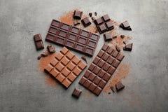 Generi differenti di cioccolato su fondo grigio immagine stock