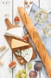 Generi differenti di formaggi baguette, vino, fichi ed uva immagini stock
