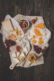 Generi differenti di formaggi con i frutti e di spuntini sulla tavola scura di legno fotografie stock