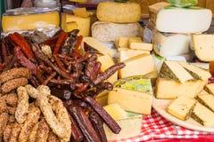 Generi differenti di formaggio e di salsiccie affumicate da vendere su un segno Immagine Stock Libera da Diritti