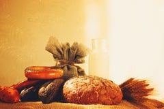Generi differenti di pane fresco e di bottiglia di latte, primo mattino, luce solare Fotografia Stock