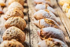 Generi differenti di pane fresco sulla tavola di legno Assortimento isolato di pane su fondo marrone immagini stock