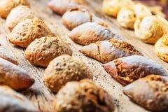 Generi differenti di pane fresco sulla tavola di legno Assortimento isolato di pane su fondo marrone immagine stock