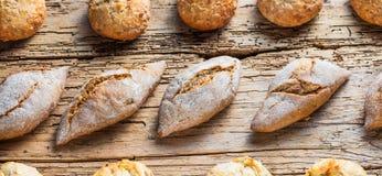 Generi differenti di pane fresco sulla tavola di legno Assortimento isolato di pane su fondo marrone immagine stock libera da diritti