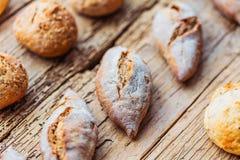 Generi differenti di pane fresco sulla tavola di legno Assortimento isolato di pane su fondo marrone fotografie stock libere da diritti