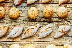 Generi differenti di pane fresco sulla tavola di legno Assortimento isolato di pane su fondo marrone immagini stock libere da diritti