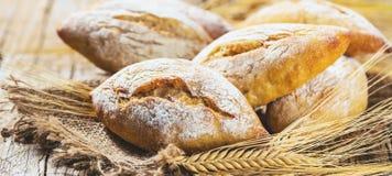 Generi differenti di pane fresco sulla tavola di legno Assortimento isolato di pane su fondo marrone fotografia stock