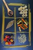 Generi differenti di pasta, cucchiai di legno con le spezie, fondo degli ingredienti alimentari, immagine della foglia di alloro  Immagine Stock Libera da Diritti