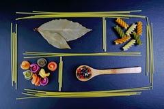 Generi differenti di pasta, cucchiai di legno con le spezie, fondo degli ingredienti alimentari, immagine della foglia di alloro  Immagini Stock