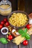 Generi differenti di pasta, di pomodori ciliegia, di basilico e di spezie sulla a Fotografia Stock Libera da Diritti
