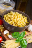 Generi differenti di pasta, di pomodori ciliegia e di spezie su una b scura Fotografia Stock