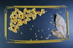 Generi differenti di pasta, fondo della foglia di alloro degli ingredienti alimentari, immagine del concetto della pubblicità in  Immagine Stock