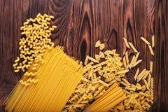 Generi differenti di pasta su un fondo di legno Rigate di Farfalle, del fettuccine, delle tagliatelle, di fusilli e del penne Ita Immagini Stock
