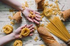 Generi differenti di pasta sulla tavola di legno, pane Immagine Stock