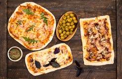Generi differenti di piccola pizza su fondo di legno rustico Varia pizza casalinga, partito di cena a casa, vista superiore fotografia stock