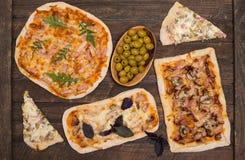 Generi differenti di piccola pizza su fondo misero rustico Varia pizza casalinga, partito di cena a casa, vista superiore fotografia stock