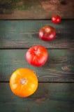 Generi differenti variopinti di pomodori su fondo di legno Immagine Stock