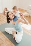 Generi divertiresi con il suo bambino mentre si siedono sulla stuoia di yoga a casa Immagine Stock Libera da Diritti