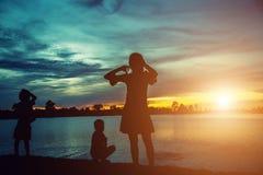 Generi e due bambini che camminano sulla spiaggia al sunse Immagine Stock