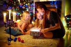 Generi e due piccole figlie che aprono un regalo magico di Natale immagini stock