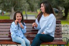 Generi e la sua piccola figlia che si siede su un banco che mangia un biscotto fotografia stock libera da diritti