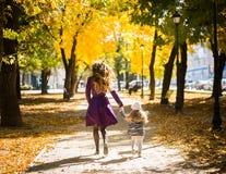 Generi e la sua ragazza del bambino che gioca insieme sulla passeggiata di autunno in natura all'aperto fotografia stock