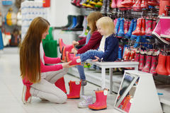 Generi e le sue due ragazze che scelgono i nuovi stivali di pioggia Fotografia Stock Libera da Diritti