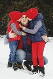 Generi ed i suoi due figli divertendosi nell'inverno nella foresta della neve Immagini Stock Libere da Diritti