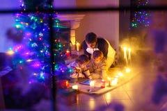 Generi ed i suoi due piccoli bambini che si siedono dal camino del camino sul tempo di notte di Natale Fotografie Stock
