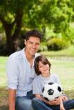 Generi ed il suo figlio con la loro sfera nella sosta Immagine Stock