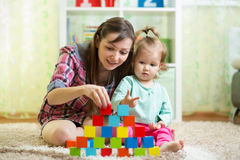 Generi ed il suo gioco del bambino con i giocattoli all'interno Fotografia Stock