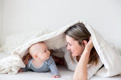 Generi ed il suo piccolo neonato, giocante insieme nel bedrroom Immagini Stock