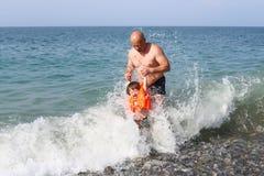Generi ed il suo piccolo nuoto del figlio nel mare dell'onda immagini stock