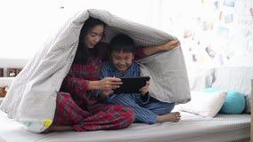 Generi ed suo figlio che guarda insieme un film sulla compressa sotto la coperta stock footage