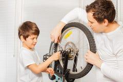 Generi ed suo figlio che ripara la bicicletta facendo uso delle pinze Immagine Stock