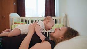 Generi i giochi con il suo bambino che mette sullo stomaco del ` s della mamma stock footage