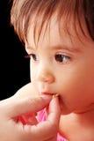 Generi il bambino affamato d'alimentazione in una priorità bassa nera fotografie stock