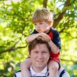 Generi il bambino di trasporto sulle sue spalle nel parco fotografia stock