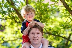 Generi il bambino di trasporto sulle sue spalle nel parco fotografia stock libera da diritti