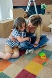 Generi il conforto di suo figlio triste che si siede sul tappeto immagini stock