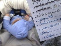 Generi il controllo della lista di acquisto mentre sta spingendo il suo bambino Immagine Stock Libera da Diritti