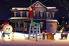 Generi il figlio che mette sulle luci intorno alla casa per il Natale Fotografie Stock Libere da Diritti