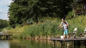 Generi il figlio d'istruzione per pescare allo stagno d'acqua dolce stock footage