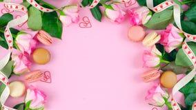Generi il fondo del giorno del ` s delle rose e dei biscotti rosa del macaron sulla tavola di legno rosa Fotografia Stock Libera da Diritti