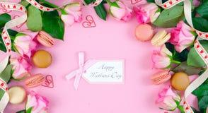 Generi il fondo del giorno del ` s delle rose e dei biscotti rosa del macaron sulla tavola di legno rosa Fotografie Stock