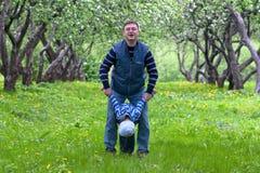 Generi il gioco con il suo figlio nel giardino della mela Fotografia Stock