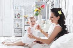 Generi il gioco con una figlia di un anno sul letto Fotografia Stock