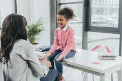 Generi il gioco del picchiettio un dolce con la piccola figlia nell'ufficio di affari fotografia stock