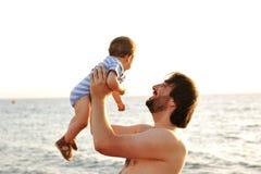Generi il lancio del suo bambino in su nell'aria Immagine Stock