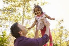 Generi il lancio di sua figlia giovane nell'aria in un parco Fotografia Stock